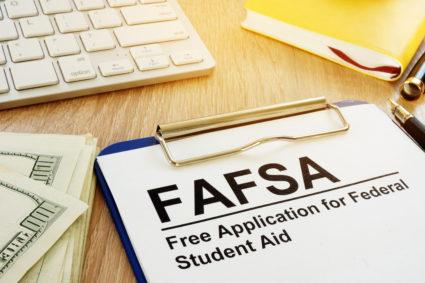 Free Application for Federal Student Aid (FAFSA) application with money.