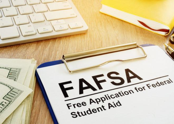 FAFSA on clipboard on computer desk with cash