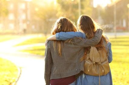 Affectionate friends walking at sunset on a college campus.