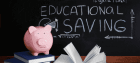 Education savings written on a chalkboard with a piggy bank in front.