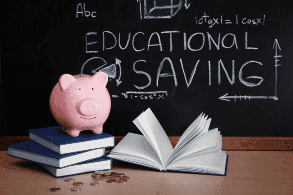 Piggy bank on a stack of books with Educational Savings written on a blackboard in the background.