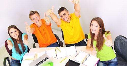 A coupe of college students working on financial aid appeal letters giving a thumbs up.