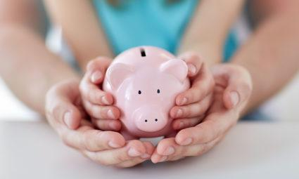 Close up of father and daughter hands holding pink piggy bank.