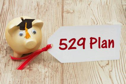 Your 529 education savings plan, A golden piggy bank and grad cap on a desk with a gift tag with text 529 Plan.