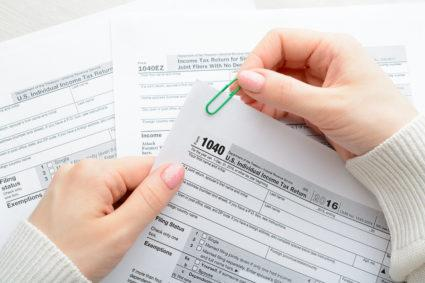 A woman holding IRS 1040 tax forms.