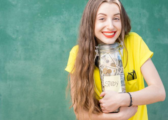 Young and happy woman in yellow t-shirt holding a bottle with money savings for study