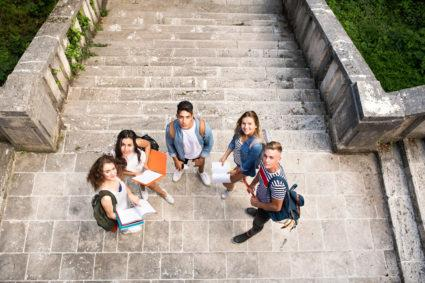 A group of college students standing on the stairs of a college campus and looking up.