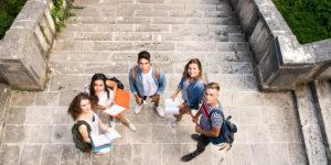 Group of attractive teenage students at the stone steps in front of university.