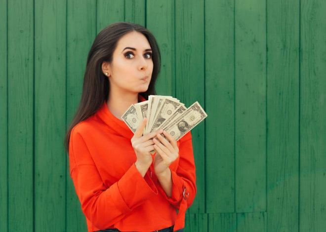 99529514 - funny casual girl holding money thinking to invest
