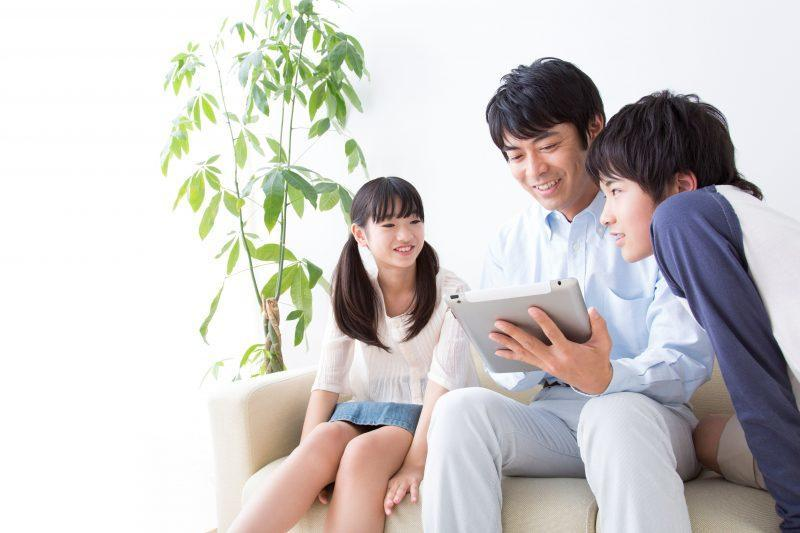 Asian family looking at handheld device.