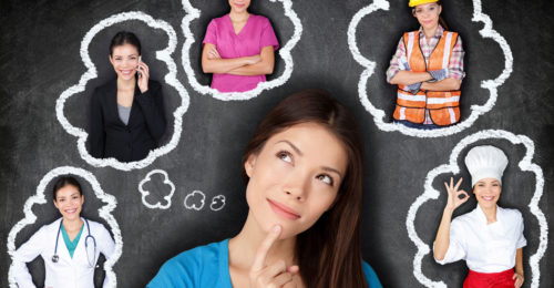 Young Asian woman contemplating career options smiling looking up at thought bubbles on a blackboard with different professions