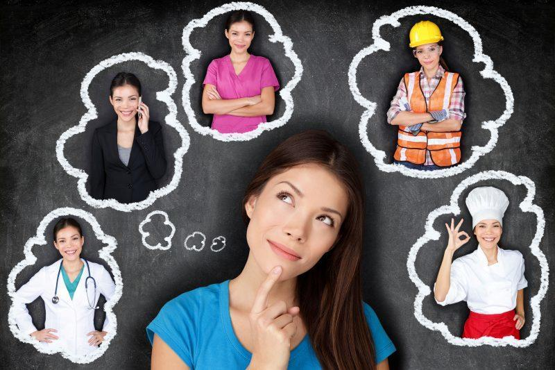 Young Asian woman contemplating career options smiling looking up at thought bubbles on a blackboard with different professions.