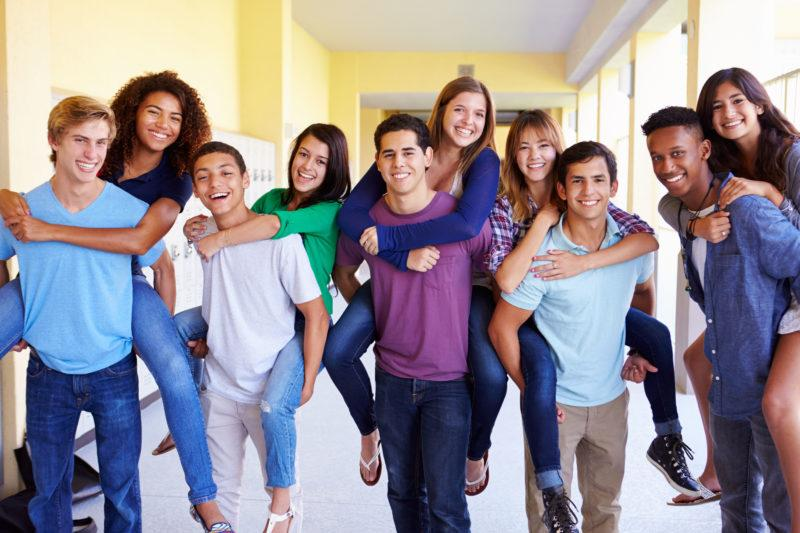 A group of smiling high school students in a hallway.
