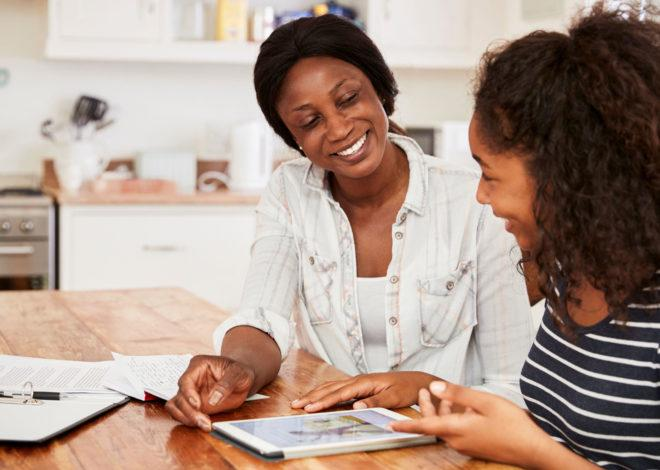 African American mother and daughter looking at a laptop.