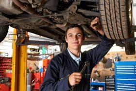 An apprentice mechanic working on a vehicle.
