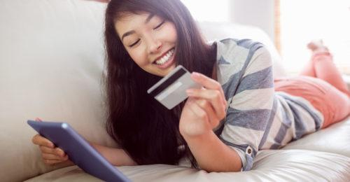 Smiling asian woman on couch using tablet to shop online at home in the living room