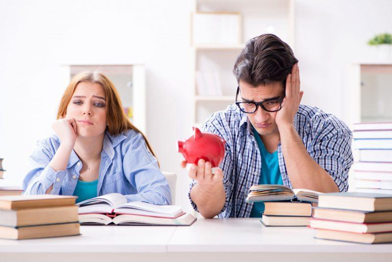 College students sitting at a table with an empty piggy bank.