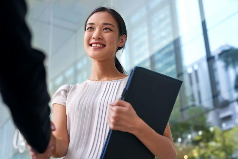 Beautiful Asian Chinese business woman shaking hands in modern city work office.