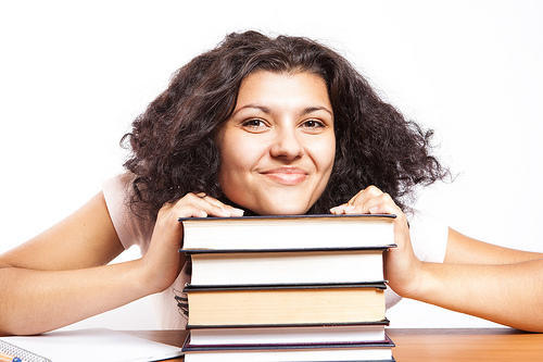 Girl smiling with books.