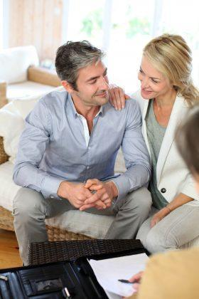 Happy couple in their mid-40's in home consultation.