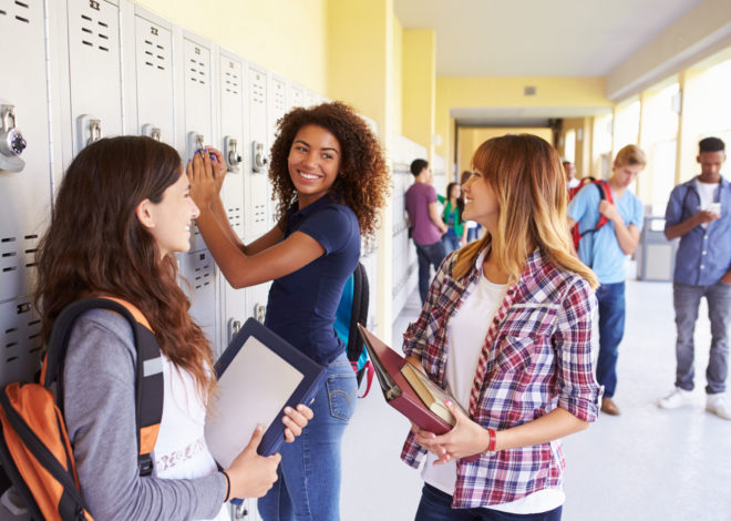 High School girls meeting at a locker and smiling.