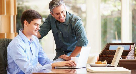 Father and son looking at a laptop and smiling.