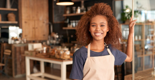 Portrait of an attractive young woman standing in front of a cafe