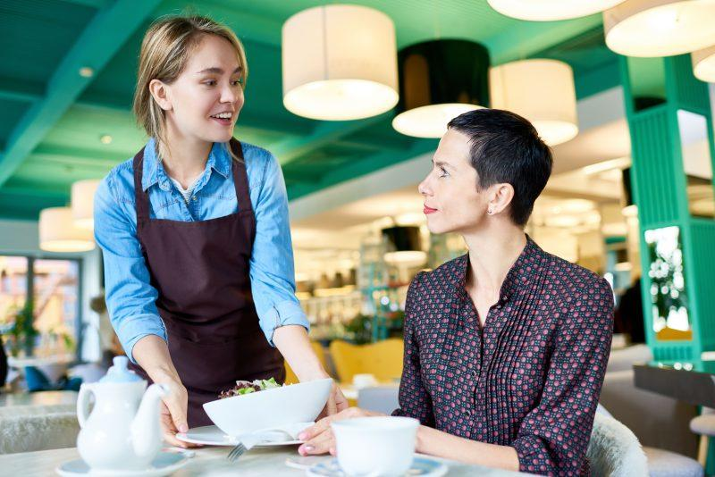A young waitress serving a customer at a restaurant.